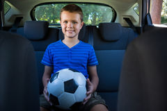 Happy teenage boy sitting with football in the back seat of car Royalty Free Stock Image
