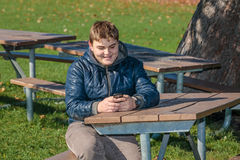 happy teenage boy sitting relaxing in autumn park and sending text messages on cellphone Royalty Free Stock Images