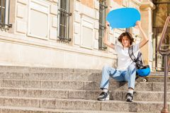 Happy teenage boy with blue blanked speech bubble. Happy teenage boy sitting on the stairs outdoors, holding blue blanked speech bubble over head Stock Photos