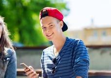 Happy teenage boy with smartphone outdoors Stock Photo