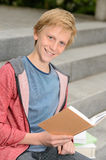 Happy teenage boy studying sitting on stairs Royalty Free Stock Photos
