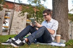 Happy teenage boy with tablet pc and coffee Royalty Free Stock Images