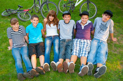 Happy teenage boys and girls resting in the grass. After riding bicycles royalty free stock image