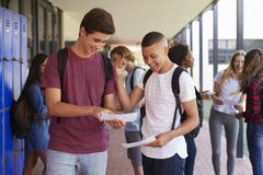 Happy teenage boys sharing exam results in school corridor Royalty Free Stock Photo