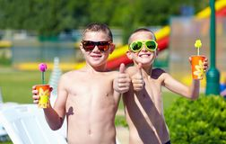 Happy teenage boys showing thumbs up in aquapark Royalty Free Stock Photo