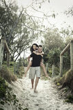 Happy teenage couple. Walking barefoot on sandy path; male giving woman a piggy back Royalty Free Stock Images