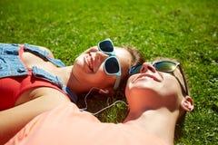 Happy teenage couple with earphones lying on grass Stock Photo