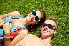 Happy teenage couple with earphones lying on grass Stock Photos