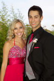 Happy Teenage Couple Going to the Prom. A beautiful blonde high school senior going to the prom with her boyfriend. She is wearing a long red prom dress and he Stock Photos