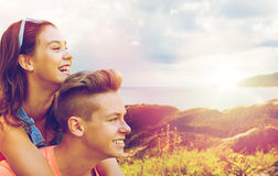 Happy teenage couple having fun outdoors. Summer holidays, love and people concept - happy smiling teenage couple having fun over island and sea background Royalty Free Stock Photo