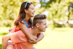 Happy teenage couple having fun at summer park. Holidays, vacation, love and people concept - happy smiling teenage couple having fun at summer park Stock Photo