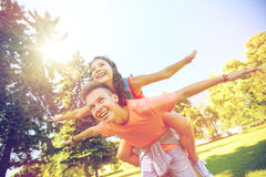 Happy teenage couple having fun at summer park. Holidays, vacation, love and people concept - happy smiling teenage couple having fun at summer park Royalty Free Stock Photos