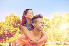 Happy teenage couple having fun at summer park. Holidays, vacation, love and people concept - happy smiling teenage couple having fun at summer park Royalty Free Stock Images
