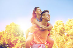 Happy teenage couple having fun at summer park. Holidays, vacation, love and people concept - happy smiling teenage couple having fun at summer park Stock Photos