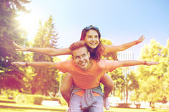Happy teenage couple having fun at summer park. Holidays, vacation, love and people concept - happy smiling teenage couple having fun at summer park Stock Images