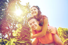 Happy teenage couple having fun at summer park. Holidays, vacation, love and people concept - happy smiling teenage couple having fun at summer park Stock Image