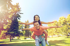 Happy teenage couple having fun at summer park. Holidays, vacation, love and people concept - happy smiling teenage couple having fun at summer park Royalty Free Stock Photo