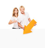 Happy teenage couple holding thumbs up and an arrow Stock Photos