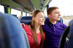 Happy teenage couple or passengers in travel bus. Transport, tourism, road trip and people concept - happy teenage couple or tourists hugging in travel bus and Stock Photo