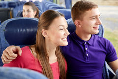 Happy teenage couple or passengers in travel bus Stock Images