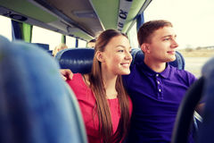 Happy teenage couple or passengers in travel bus. Transport, tourism, road trip and people concept - happy teenage couple or tourists hugging in travel bus and Royalty Free Stock Photos