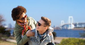 Happy teenage couple in shades having fun outdoors. Friendship, travel, tourism and people concept - happy international teenage couple in shades having fun over Stock Image
