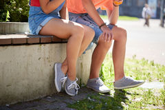Happy teenage couple sitting on city street bench Royalty Free Stock Photography