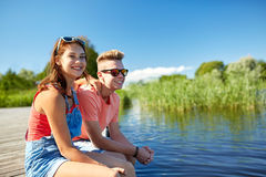Happy teenage couple sitting on river berth Royalty Free Stock Photos