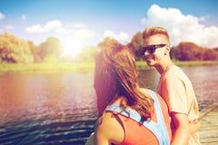 Happy teenage couple sitting on river berth Stock Photos
