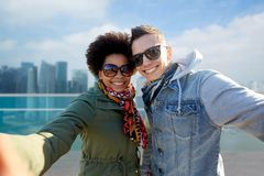 Happy teenage couple taking selfie in singapore Stock Images