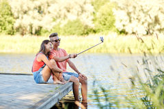 Happy teenage couple taking selfie on smartphone Royalty Free Stock Images
