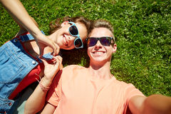 Happy teenage couple taking selfie on summer grass. Love and people concept - happy teenage couple in sunglasses lying on grass and taking selfie at summer Stock Images