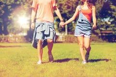 Happy teenage couple walking at summer park Stock Photos