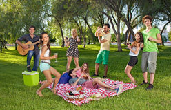 Happy teenage friends enjoying a picnic outdoors. Group of lively happy teenage young friends enjoying a picnic outdoors dancing and singing along to guitar royalty free stock photography