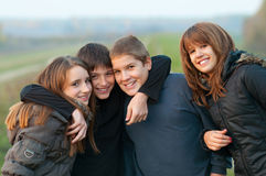 Happy teenage friends having fun outdoor. Group of smiling teenage friends having fun outdoor on cloudy autumn day royalty free stock image