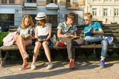Happy 4 teenage friends or high school students are having fun, talking, reading phone, book. Friendship and people concept, city. Street background stock photos