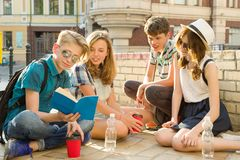 Happy 4 teenage friends or high school students are having fun, talking, reading phone, book. Friendship and people concept, city. Street background royalty free stock image