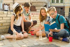 Happy 4 teenage friends or high school students reading books. Friendship and people concept royalty free stock image