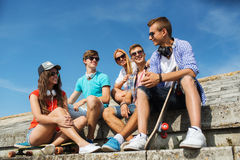 Happy teenage friends with longboard on street. People, leisure and sport concept - group of happy teenage friends with longboard and headphones talking on city Royalty Free Stock Photos