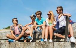 Happy teenage friends with longboard on street Stock Photo