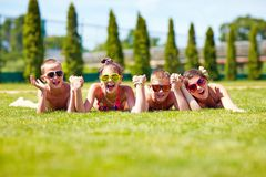 Happy teenage friends lying on summer lawn Stock Photos