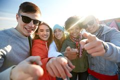 Happy teenage friends pointing fingers on street Stock Photography
