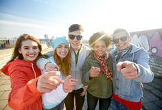 Happy teenage friends pointing fingers on street Royalty Free Stock Images