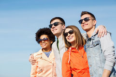 Happy teenage friends in shades hugging outdoors Stock Images