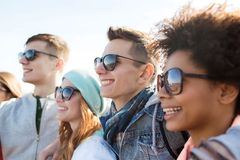 Happy teenage friends in shades hugging outdoors Stock Photos
