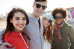 Happy teenage friends in shades hugging outdoors Royalty Free Stock Image