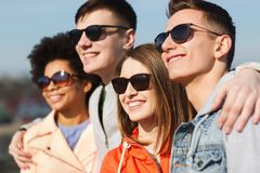 Happy teenage friends in shades hugging outdoors Stock Photo