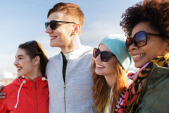 Happy teenage friends in shades hugging outdoors Royalty Free Stock Images