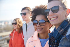 Happy teenage friends in shades hugging on street Stock Photos