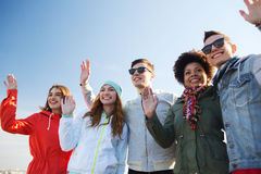 Happy teenage friends in shades waving hands Stock Photo